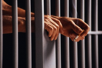 Prisoner Holding Cigarette Between Bars