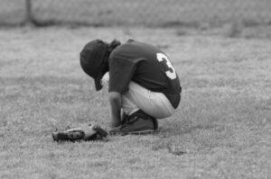 kid boy kneeling field sad
